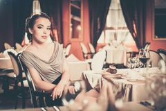 Girl alone in a restaurant Stock Images