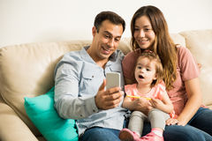 Girl amazed with family selfie. Surprised Latin girl and pretty mother with something that his dad is showing them through his cell phone Stock Photos