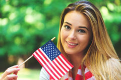 GIrl with an American flag on the fourth of July Stock Images