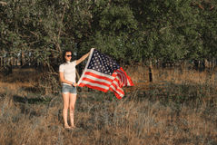 The girl with the American flag outdoors, stars and stripes flag flutters in the wind, Royalty Free Stock Photos