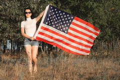 The girl with the American flag outdoors, stars and stripes flag flutters in the wind, Stock Photo