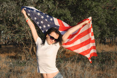 The girl with the American flag outdoors, stars and stripes flag flutters in the wind, Stock Photos