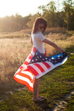 The girl with the American flag outdoors, stars and stripes flag flutters in the wind, Stock Image