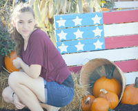 Girl, American Flag Pallet, Pumpkins. A girl by an autumn display of pumpkins and an American Flag made from a wooden pallet Royalty Free Stock Photos