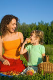 Girl And Young Women Eats Fruits On Picnic Royalty Free Stock Photography