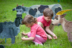 The girl anf the boy feed wooden sheeps and cow Royalty Free Stock Photo