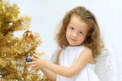 The girl - angel. Decorating a christmas tree Stock Image