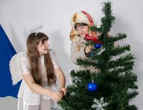 A girl in an angel costume and a woman decorate a Christmas tree Royalty Free Stock Photo