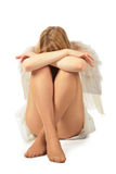 Girl in angel's costume sits face in knees Stock Photos
