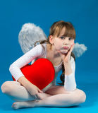 Girl angel Valentine's day. Angel girl sitting and holding a big heart Royalty Free Stock Images