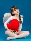 Girl angel Valentine's day. Angel girl sitting and holding a big heart Stock Photos