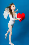 Girl angel Valentine's day. Angel girl in a white suit holding a big heart Stock Images