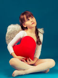 Girl angel Valentine's day retro. Angel girl sitting and holding a big heart Stock Image