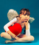 Girl angel Valentine's day retro. Angel girl sitting and holding a big heart Royalty Free Stock Photos