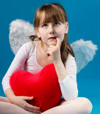 Girl angel Valentine's day retro. Angel girl sitting and holding a big heart Stock Images