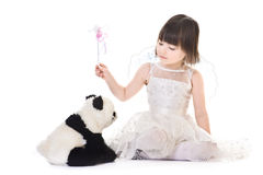 Girl with angel wings casting spell on a panda. Little girl with angel wings casting spell on a panda Royalty Free Stock Images