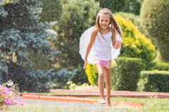 Girl with angel wings running around in the rain in the garden. Happy six year old girl dressed as an angel with wings is walking with splashes of water for Stock Images