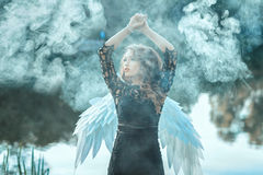Girl with angel wings is shrouded in smoke. Stock Photos