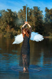Girl with angel wings standing near a pole dance. Stock Photography