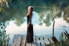 Girl with angel wings standing on the pier and smiling. Royalty Free Stock Image