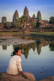Girl at Angkor Wat. Girl sitting on a rock above the pool and posing for a photo at Angkor Wat, Cambodia Stock Photography
