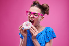 Girl angrily biting a sprinkled doughnut Royalty Free Stock Photos