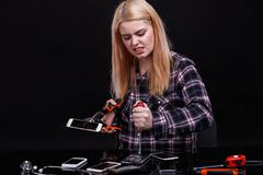 A girl, angrily breaks smartphones with the construction clamp and a screwdriver. On a black background. Royalty Free Stock Image