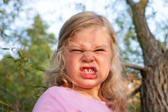 Girl is angry. Girl in front of nature background is angry stock image
