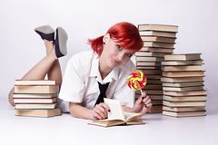 The girl in anime style with candy and books. Red-haired girl, style of anime, non-standard, piercings on his face, blue eyes, earrings tunnels, bright lollipop royalty free stock image