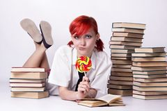The girl in anime style with candy and books. Red-haired girl, style of anime, non-standard, piercings on his face, blue eyes, earrings tunnels, bright lollipop royalty free stock images