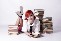 The girl in anime style reading a book. Red-haired girl, style of anime, non-standard, piercings on his face, blue eyes, earrings tunnels, photo in bright colors royalty free stock image