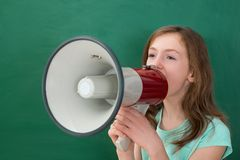 Girl Announcing On Megaphone. Against Chalkboard In Classroom Royalty Free Stock Images