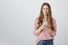 Girl is annoyed with spam on her mailbox. Portrait of bothered and confused caucasian woman holding smartphone, looking. Displeased at camera, feeling disgust stock photo