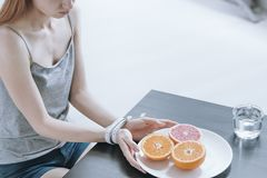 Girl keeping restricted diet. Girl with anorexia at wooden table with orange on plate keeping restricted diet. Eating disorders concept Stock Images