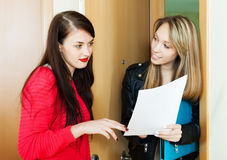 Girl answer questions of visitor with papers at home Royalty Free Stock Photos