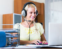 Girl answering the call of technical support and smiling Royalty Free Stock Photography