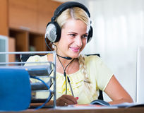 Girl answering the call of technical support and smiling Stock Photography