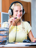 Girl answering the call of technical support and smiling Royalty Free Stock Photo