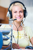 Girl answering the call of technical support and smiling Royalty Free Stock Images