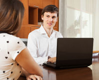 Girl answering to outreach worker. Girl answer questions of outreach worker with laptop in home or office Royalty Free Stock Photos