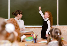 Girl answers questions of teachers near a school board.  Stock Images