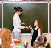 Girl answers questions of teachers near a school board.  Royalty Free Stock Image