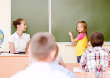 Girl answers questions of teachers near a school board Stock Photo