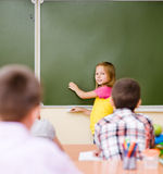 Girl answers questions of teachers near a school board Royalty Free Stock Photography