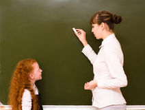 Girl answers questions of teachers near a school board Stock Photography