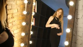 Pregnant looking in the mirror stock footage