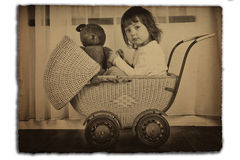 Girl in antique baby carriage. Young girl in an antique wicker baby carriage with teddy bear.  Old sepia photo Royalty Free Stock Images