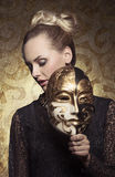 Girl in antique carnival portrait. Carnival portrait of masquerade blonde woman with antique baroque lady style and venetian mask in the hand. Gothic lace dress Royalty Free Stock Images
