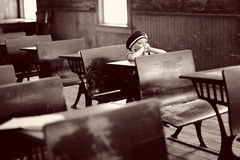 Girl at antique school desk. Girl sitting at an antique desk in an old school classroom.  Sepia color modified Stock Photography