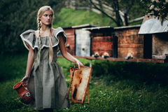 The girl on an apiary. Carries a pitcher and a framework with honey. In the distance there are a bee skeps Royalty Free Stock Photo